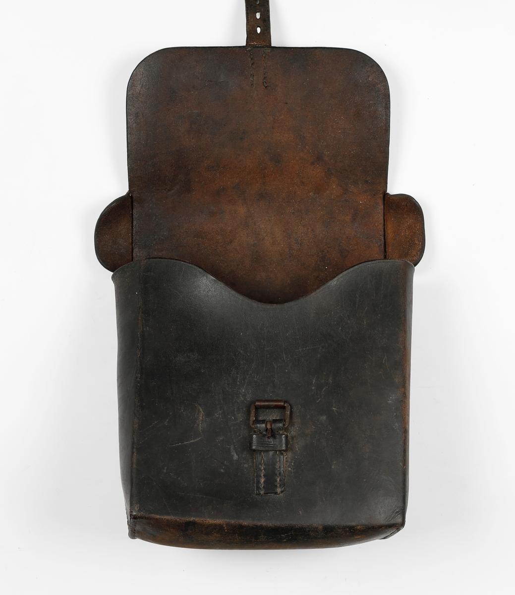 Tysk verktøyveske for linjemann i mørk brun lær. Linjemann la opp linje til felttelefoner. Brukt under andre verdenskrig. Lærhempe til å ha en blyant i på innsiden.
