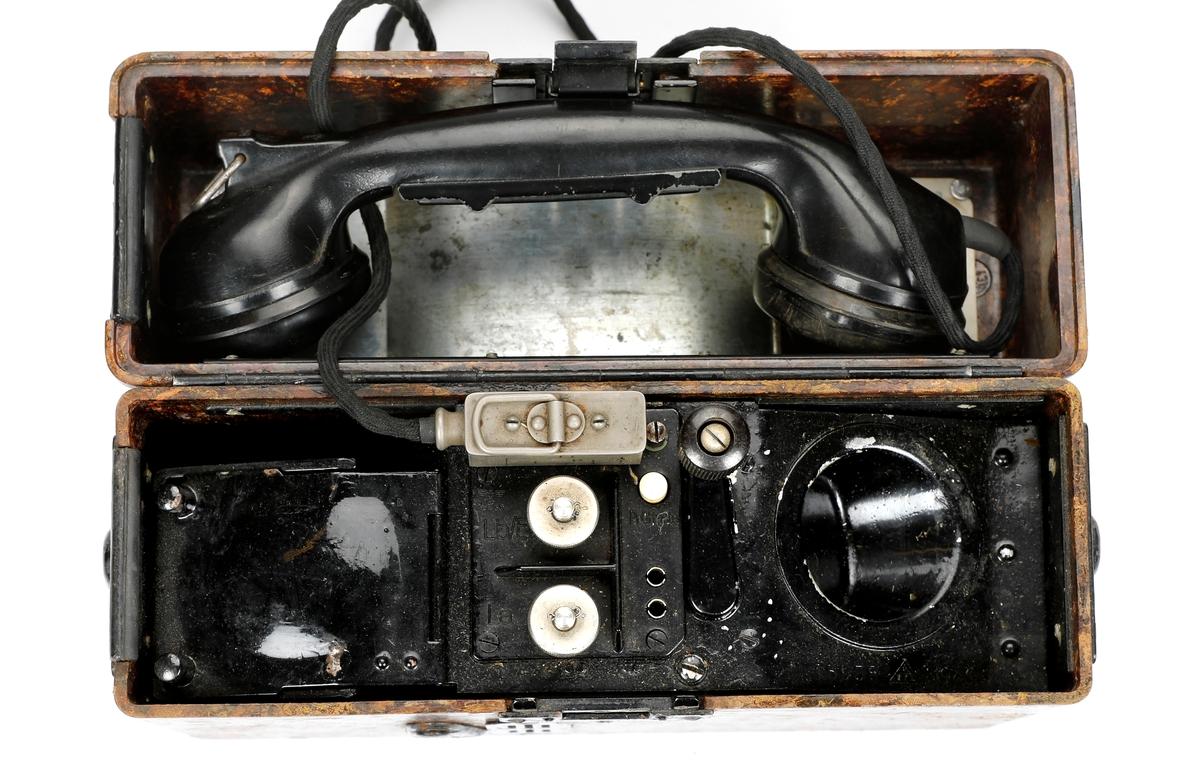 Tyskprodusert felttelefon FF33 (Feldfernsprecher 33). Telefonen er innebygd i en bakelittkasse og mangler bæresele. På lokket er det montert en metallplate med fonetisk alfabet og uttale til ordene og en hvit kodeplate.