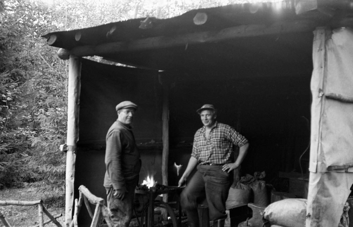 Jørgen Øiseth og Arne Kalbakken i et skjul av presenning og tømmer. Esse. Åsumdammen (Åssum?) ved Glomma, Kongsvinger, Hedmark.