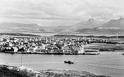 Bodø tatt fra Nyholmen. En dampbåt seiler innover mot kaia.