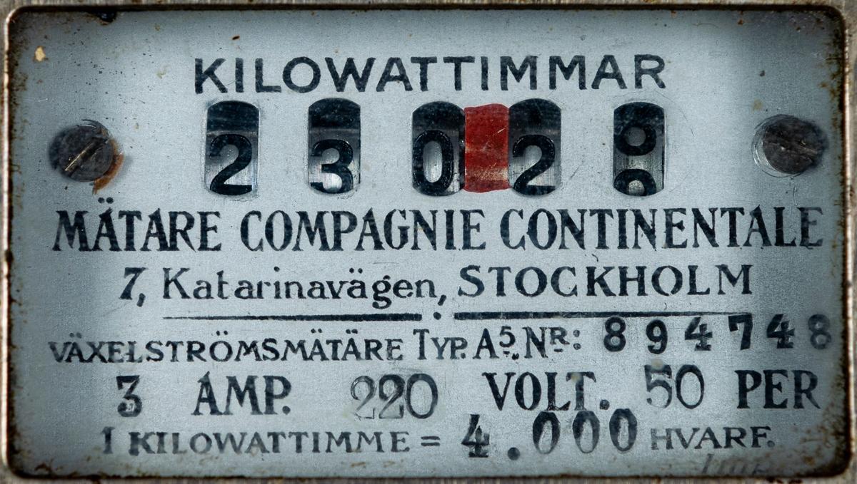 """Mätartavla, trä, järn, porslin m.m. 2 uppsättningar säkringselement i porslin. Strömbrytare i backelit (?). Sladdstumpar 2 plåtbrickor med text """"SÖDERHAMNS ELEKTROCITETSVERM No 2596"""" och """"VID FEL PÅ BELYSNINGEN RING TELEFON 310.910.421. SÖDERHAMNS ELEKTRISKA BYRÅ P.A. JOHANSSON""""."""