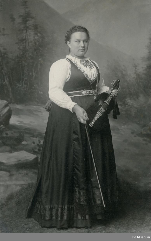 Kvinne i stakk og liv og hardingfele; Aslaug H. Borgja, gift Sannes, ståande i fotoatelier.