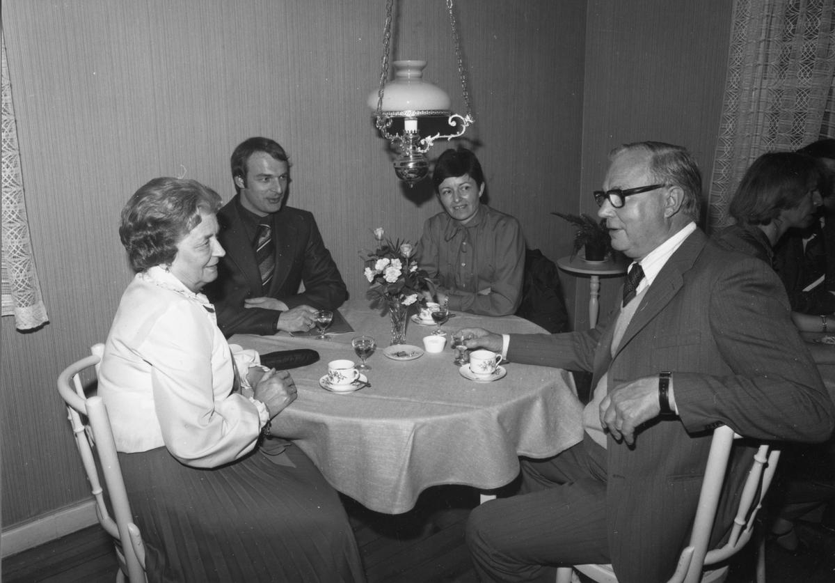 Två kvinnor och två män sitter runt ett bord och dricker kaffe med avec.
