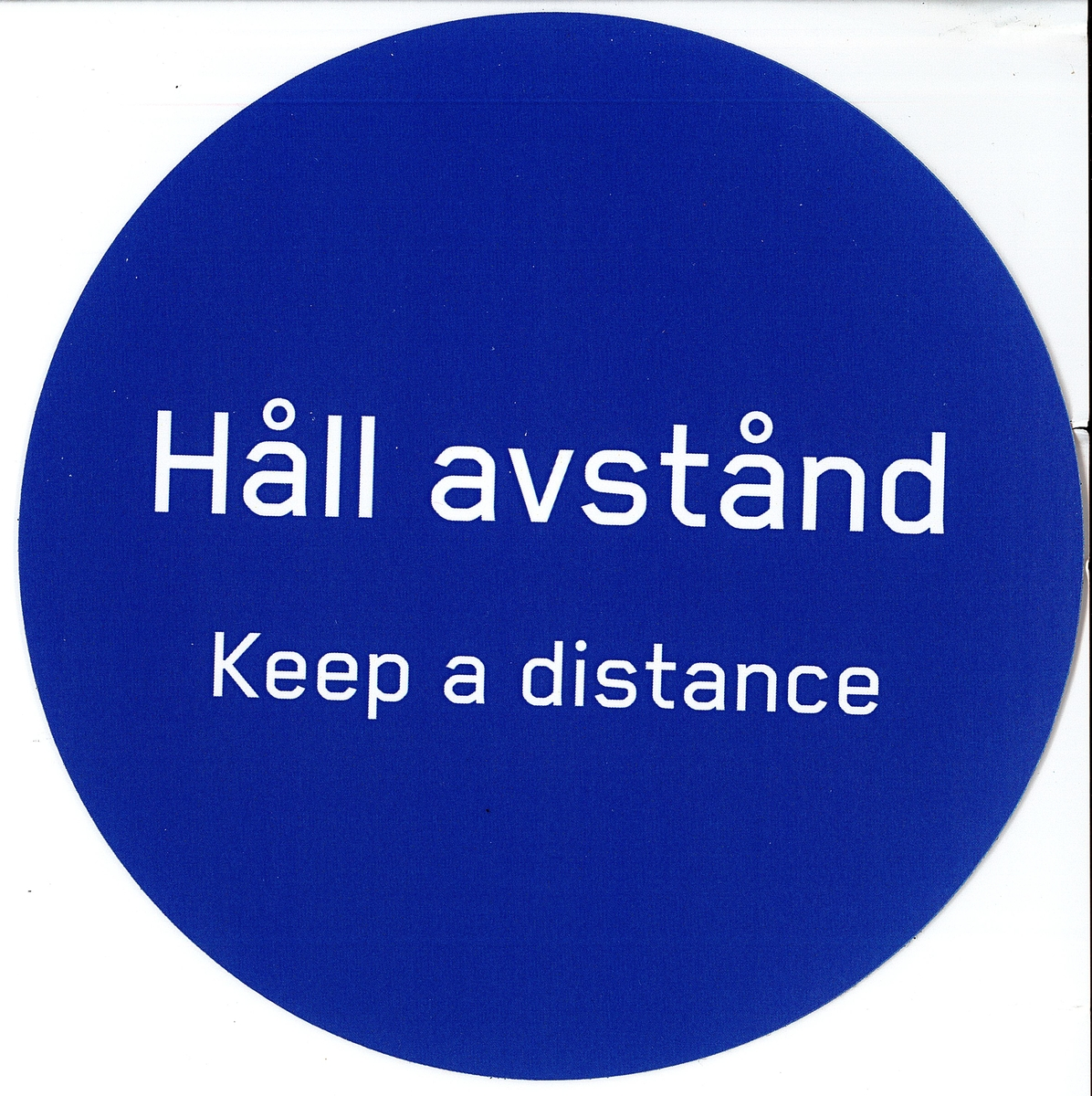 "Blå rund klisterdekal med texten ""Håll avstånd Keep a distance"". Vit baksida."