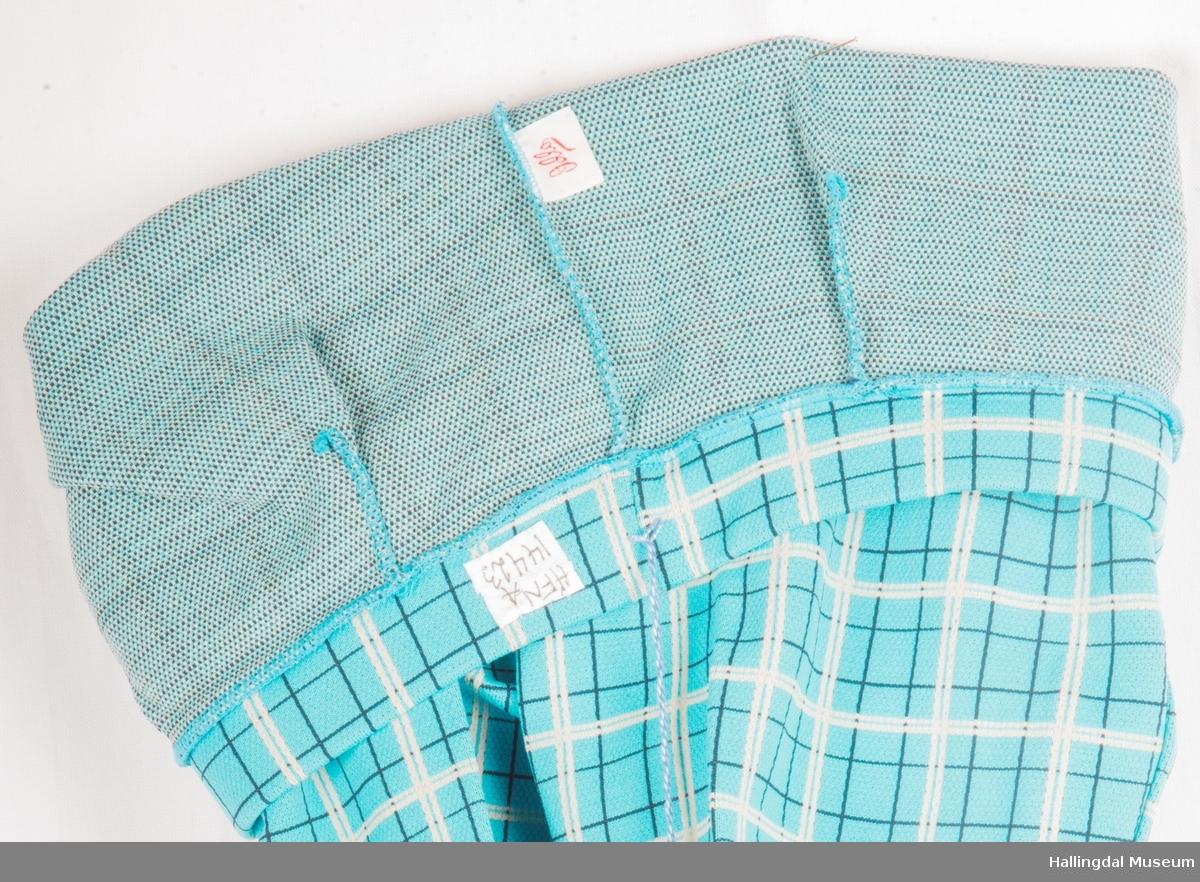 Tyrkis strekkbukse i rutemønster av hvite og svarte striper.  Buksen er til å trekke på seg.