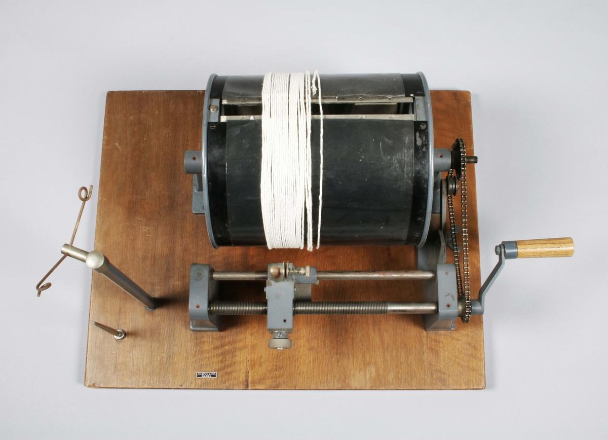 """Kontrollhaspel. På en rektangulär ekplatta, monterad en svart, genombruten trumma, som på höger sida, har en kedja med handvev för drivning. Veven förbinds med en lång, skjutbar, gängad stav, där garnet löper, som rullas upp på trumman. På vänster sida, två vertikala stänger, en för garnrulle. Medföljer, två svarta papperskartor och en bunt beigabruna papperskartor, som fästes runt trumman. Märkt med etikett: N. ZIVY & Co BASEL. Proveniens Verner Frang AB, Borås.  Funktion: För att kontrollera garnets jämnhet  Bolaget """"Verner Frang AB"""" verkade som agent och distributör av industrigarner till den svenska textilindustrin och representerade ett flertal spinnerier i Europa såsom Enka Glanzstoff, Marzotto, Kunert med flera.  I början av 1980-talet såldes bolaget till invenstmentbolaget Parlamentet som sedermera tillsammans med ytterligare fyra textilföretag bildade Percalgruppen och introducerades på börsen."""