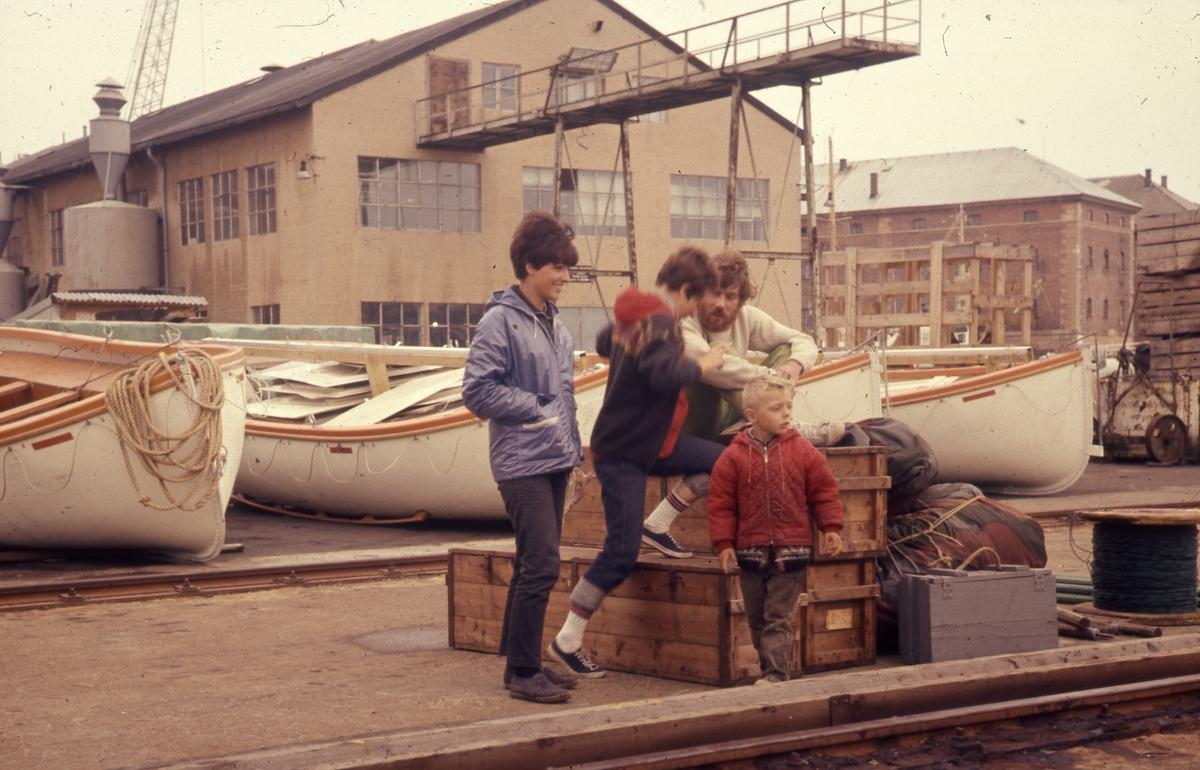 Felt 1967. Hjemtransport. Havn med båter. Kasser Feltutstyr Sybil Rita Stephen.