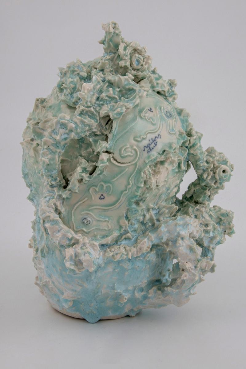Håndmodellert porselensskulptur med sjøgrønn og lys turkis glasur. Skulpturen har havhestmotiver i relieff og er utformet som et koralrev, men med referanser til kanneformen. Sammen med havhestene finner vi et anker, et hjerte og påskriften Sailors Club i koboltblå underglasur. På baksiden en medlajong med kunsntnerens navn og datering i relieff.