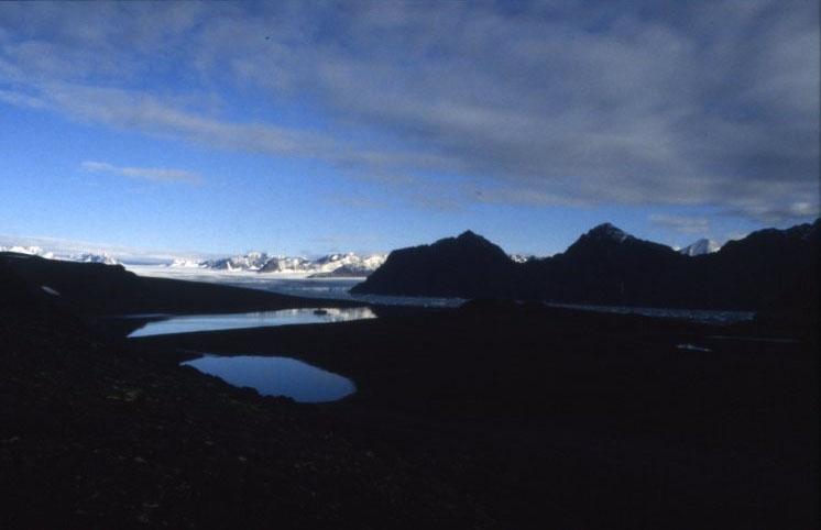 På väg upp på Dronning Mauds fjell, Mitrahalvöya, sydvästra Spetsbergen. I Signehamna syns en liten mörk fläck, det är expeditionsfartyget M/S Origo