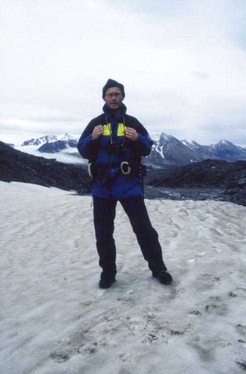 En man med mindre ryggsäck står på ett snöklätt berg, Dronning Mauds fjell. Han bär Svenska Polarforskningssekretariatets klädsel.