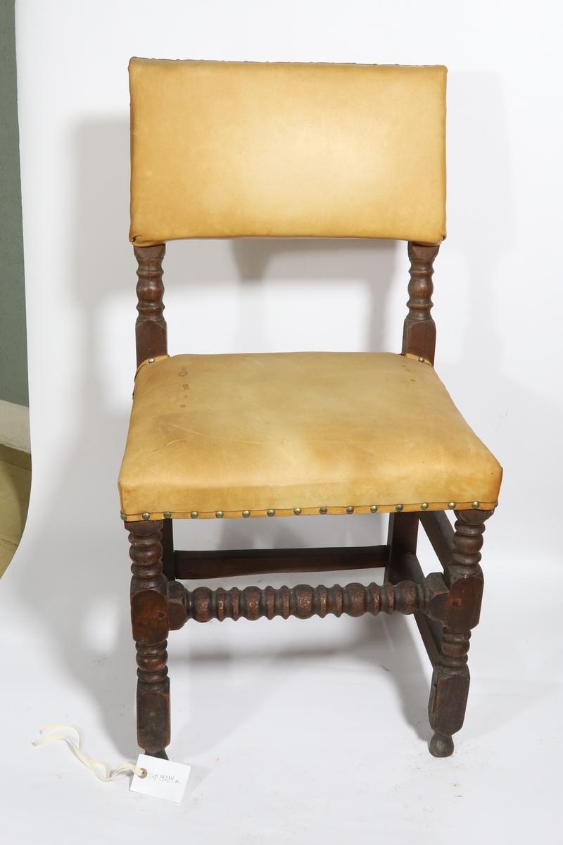 Stoler med dreide ben. Rektangulært sete, polstret og trukket med gult lær. Nagler fester skinnet til treverket. Stolryggen består av ramme i tre trukket med samme type lær. Rette stolben.