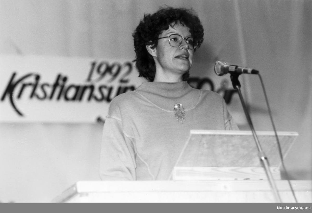 Statssekretær i Næringsdep (DNA), fra Alesund, Anne Breiby,  åpner Jappe Ippes-forestillinga i Idrettshallen, byjubileet 1992. 29. november 1992.  - 29.11. var det stor forestilling i Idrettshallen, på 300-års-dagen for byens første klippfiskeksport.  Edvard Bræins kantate til 200-års-jubileet 50 år tidligere, der Bysangen utgjør finalesatsen, ble framført av KSO og sammensatt kjempekor. Orgelpositivet fra Nordlandskirka var med. Dirigenten nektet imidlertid nærradioen å gjøre det avtalte lydopptaket som rådmannen hadde bestilt, og resultatet er at bysangen fortsatt ikke fins innspilt på bånd med kor og orkester ! På denne forestillingen ble også Klippfiskballetten framført, med en nederlender ansatt i Shell i den kostymerte rollen som Jappe Ippes/forteller. OW hadde gleden av å holde leseprøvene. Ideen var jo at han skulle høres ut slik Jappe Ippes kunne ha gjort, med sterk aksent, men det ble kanskje for mye av det gode. -- Bildet er fra avisa Tidens Krav sitt arkiv i tidsrommet 1970-1994. Nå i Nordmøre museums fotosamling.
