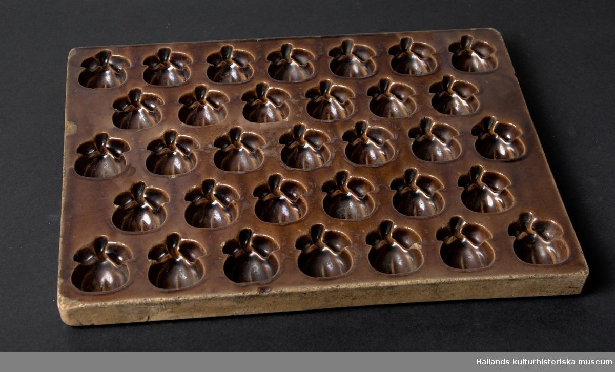 En samling bestående av fyra matriser som har använts för att tillverka former till marmeladkonfekt, samt en färdig form (a).  A: Form i brunglaserad keramik med 33 stycken äppelformade håligheter. L: 350 mm, B: 260 mm, D: 25 mm  B: Matrisform av keramik med 33 stycken geometriska mönstrade förhöjningar. L: 340 mm, B: 265 mm, D: 50 mm  C. Matrisform av keramik med 33 stycken äppelformade förhöjningar. Har använts till att pressa fram mönstret i form A. L: 360 mm, B: 282 mm, D: 60 mm  D. Matrisform av keramik med 33 stycken tandradsformade förhöjningar. L: 335 mm, B: 265 mm, D: 55 mm  E. Matrisform av keramik med 28 stycken rosformade förhöjningar. L: 360 mm, B: 282 mm, D: 45 mm