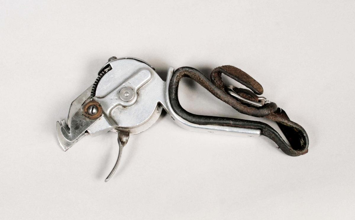 Handknytapparat. Nr. 12005. Apparaten som hålles i höger hand, knyter medelst ett enkelt handgrepp, samman de trådar som hålles i därför avsedda spår, genom mekanisk rörelse. Proveniens L.J. Wingqvist, Fritsla Mekaniska Väveri, Fritsla.  Funktion: För att knyta ihop trådar som gått av på textilmaskiner