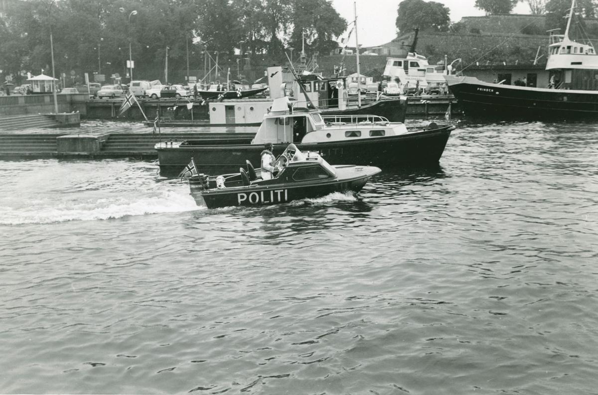 Politiorkerster spiller på kaia. Flere ulike politibåter. Akershus festning og Oslo rådhus i bakgrunnen.