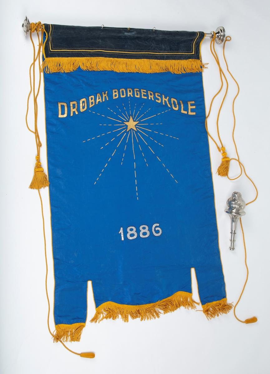 """Skolefane for Drøbak borgerskole/Drøbak høiere almenskole. Fanen laget til skolen 50-års jubileum i 1936. Silke eller kunstsilke.  Ene siden rødt stoff med malt skrift og dekorasjon i sølv og gull:  """"DRØBAK HØIERE ALMENSKOLE   Å TENKE FRITT ER STORT   Å TENKE RETT ER STØRRE"""" """"1886 23 august. 1936 23. august""""  Den andre siden blått stoff med malt dekorasjon i gull: Stjerne med stråler """"DRØBAK BORGERSKOLE""""  En mørk blå fløyelskant dekker fanen helt øverst. Denne kan være sekundær.  Fanen er utstyrt med gullsnorer og dusker. Fanen er festet til en trestang med store metallkuler i endene. Trestangen kan være sekundær da det ser ut til at metallkulene har vært festet annerledes.  Mye tyder på at fanen har vært hengt opp da det er kroker festet til stangen.  Påskrift: Drøbak Borgerskole 1886.              Drøbak høiere allmennskole              Å tenke fritt er stort              Å tenke rett er større"""