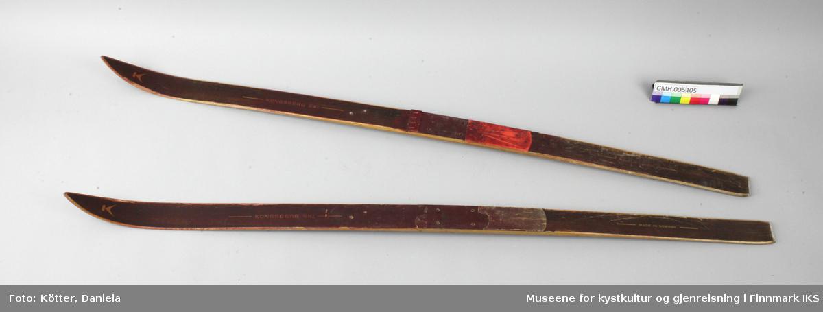 Barneskiene er av tre og er malt over med rød, halvtransparent lakk. Bindingene mangler. Bare ved en av skiene er de røde kunststoffbeleggene igjen.  Bak har skiene en metallkant.