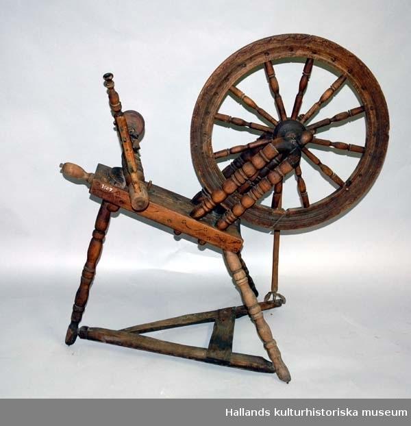 Spinnrock av trä med axlar av järn och lager för rullen av läder. Snedställt bröst. Hjulet vilar på dubbla stöd. Stjärnliknande ornament samt bågar inbrända på bröst och hjul. Märkt enligt avritad text.