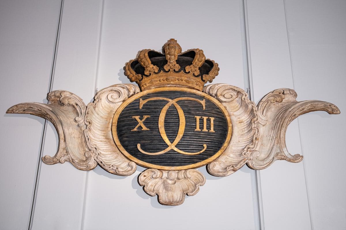 Oval söld, oval med CARL XIII:s namnchiffer på blå räfflad botten innefattad i roccailler.