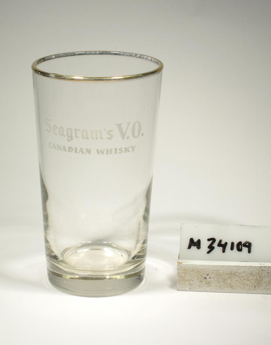"""Lätt konande kupa med guldkant runt mynningen. Tryckt text i vitt: """"Seagram's V.O. CANADIAN WHISKY""""."""