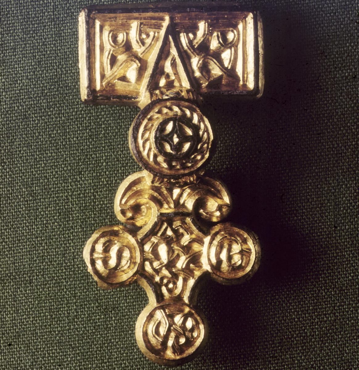Relieffspenne med runer på baksiden. Fra Eikeland.