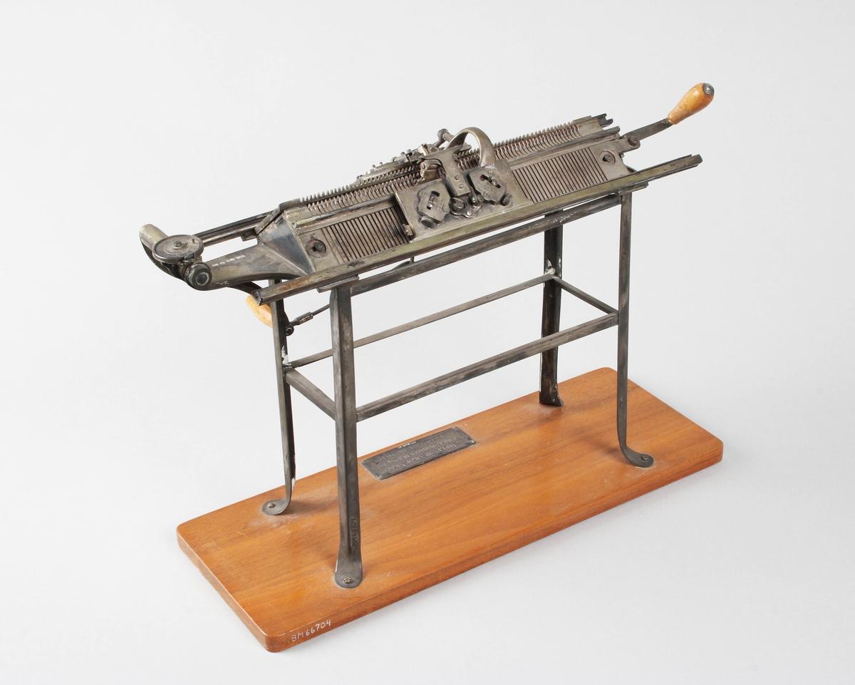 Modell av handstickmaskin. Silver, stämplad 1947. 2 nålbäddar. Handtag av svarvat trä. Står på rektangulär träplatta. Maskinen står i sin tur, på klädd platta, med grön crepe, samt garneringsband på sidorna. Förvaras inom rektangulär skyddsmonter av glas.   Märkt: Till DIREKTÖR OLOF NILSSON PÅ JUBILEUMSDAGEN DEN 17/10-1947 FRÅN SAMTLIGA ANSTÄLLDA.  Funktion: Prydnadsföremål