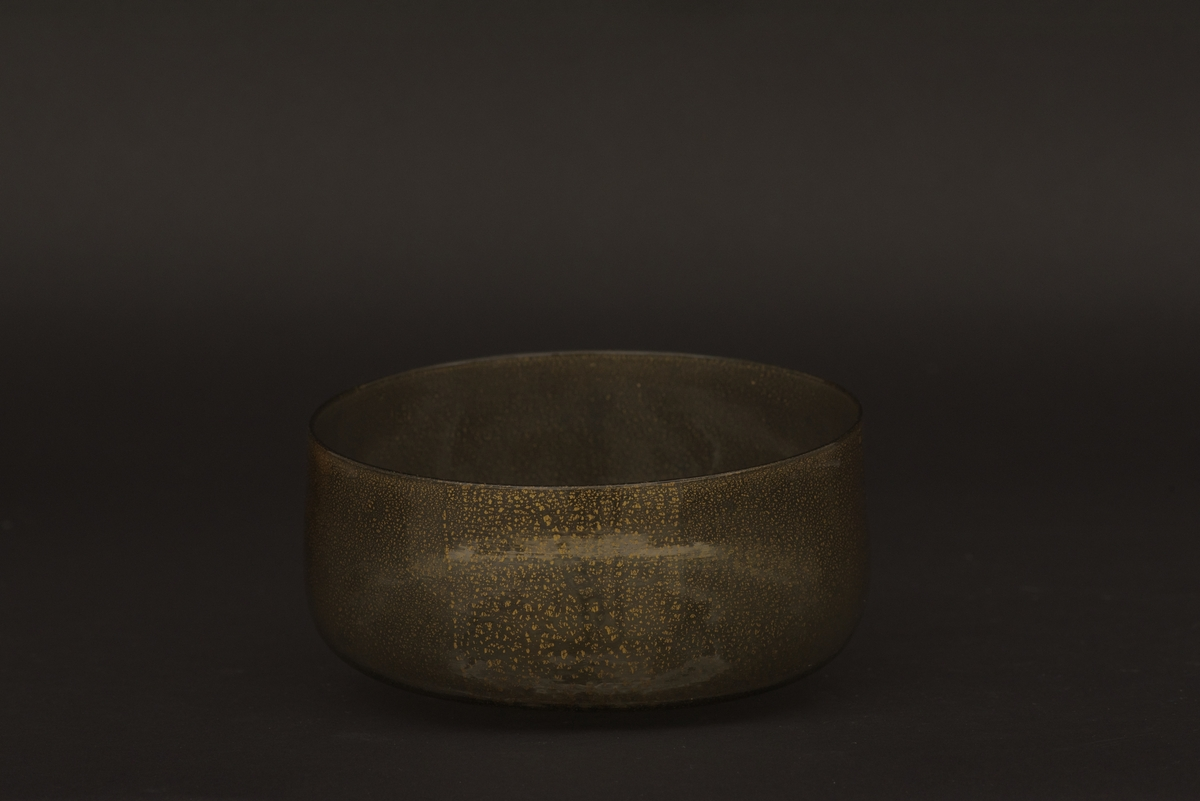 Rund glaspokal och fodral av masurbjörk. Glaset är svagt gröntonat och har insprängt guld i glasmassan, vilket tyder på att den är av venetiansk tillverkning. Pokalens fot är avslagen och fodralet är tillverkat efter att det hände. Fodralet har tidigare varit fodrat, troligen med ett filtliknande tyg. I botten ligger några bok- eller tidningssidor, från 1800-talets första del, och pokalen är fylld med bland annat fårull som stötskydd. På locket finns rester efter tre sigillstämplar i lack.