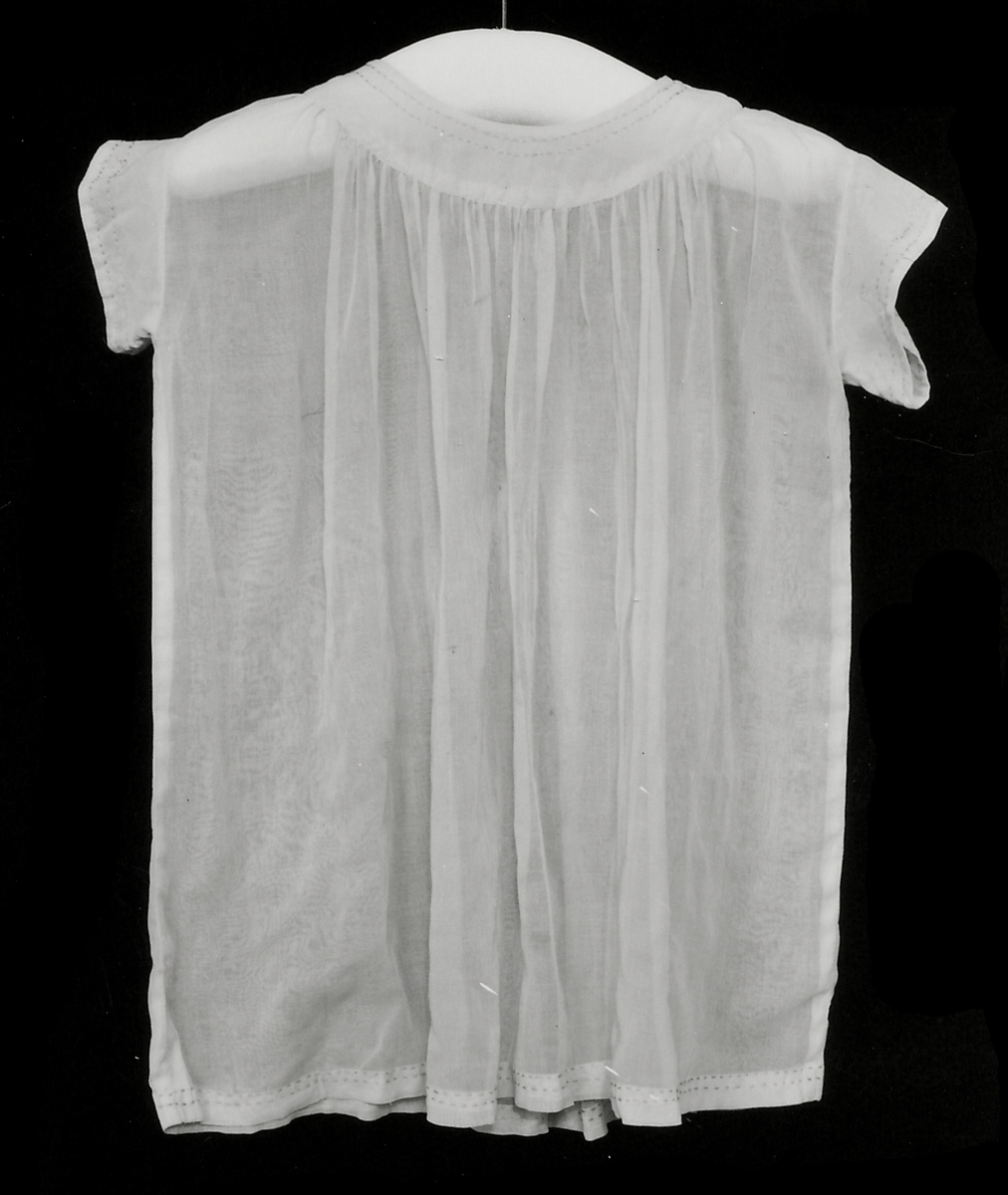 Barnklänning av aprikosfärgat, glest bomullstyg, typ batist. I halsen, runt ärmarna och nedtill dekorarad med enkla stygn. Maskinsydd. En tryckknapp i halsen.