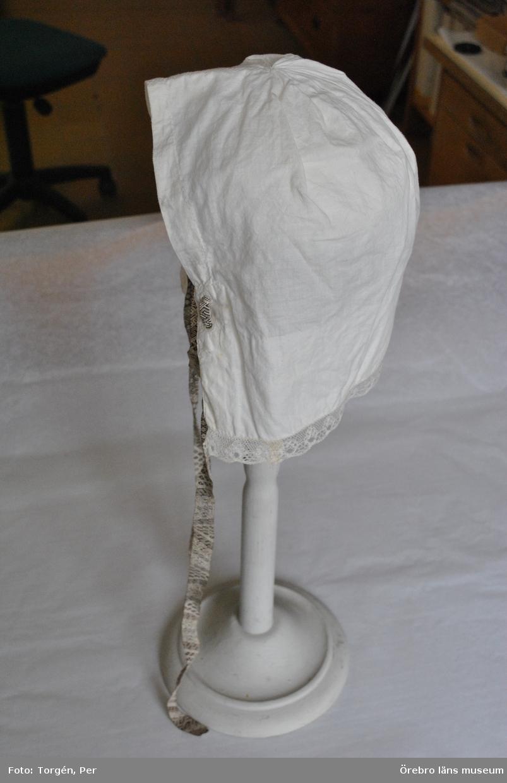 Fruntimmersmössa. Av vitt tunt bomullstyg, sydd som hätta.  Framkanten rak med bred fåll, kantad med skir, knypplad spets. Bakkanten rundad med ett veckat hoptag och söm nertill mitt bak. Sömmen har ett broderi i vit rätlinjig plattsöm. Nerkanten har bred fåll: i tränsade hål är trätt ett knytband, Leksandsband, (110 cm långt), vävt i opphämta av brunt bomullsgarn och vitt lingarn.  Mössan är handsydd.  Mössa till daladräkt, troligen Leksand.  Inga uppgifter finns om förvärvsomständigheter.