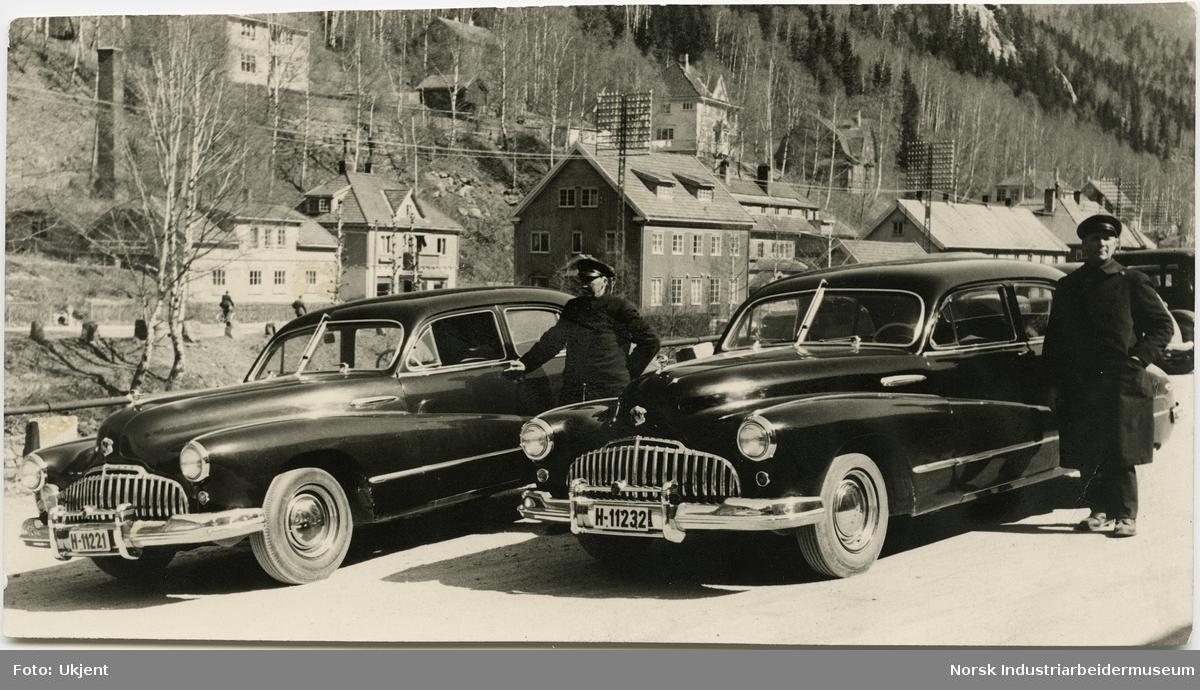 Oskar Andresen og Ole Brenden i uniform stående ved siden av hver sin bil av merket Buick. Bilene tilhører Rjukan Byanlegg og mennene var ansatt som sjåfører i Norsk Hydro.  Rjukan Varelager, slakter og bakeri i bakgrunnen. Boliger i Villaveien.