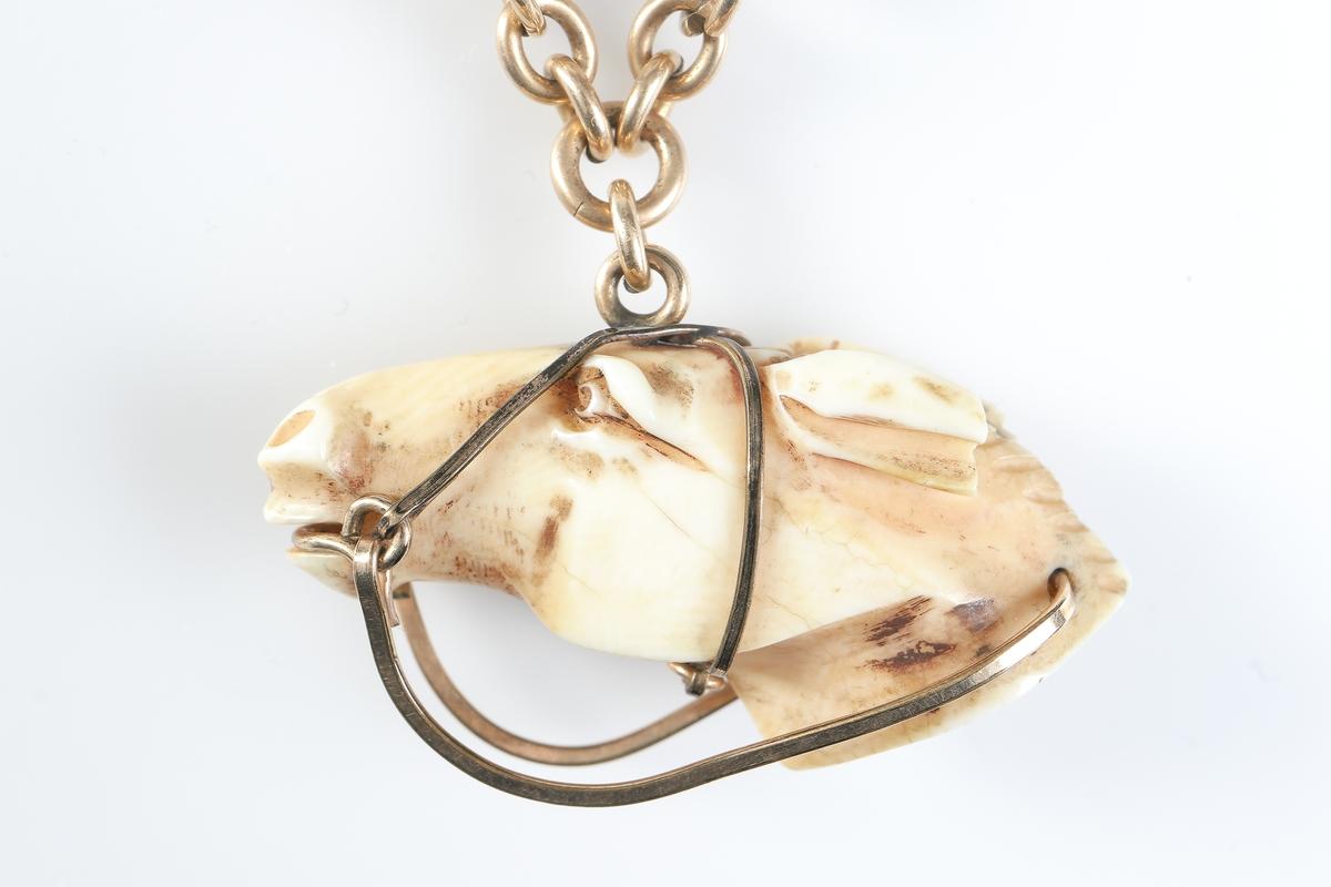 Nyckelkedja bestående av hake och kedjor i förgylld mässing, samt korslagda kors uppfästa på en hästsko. Nedtill är ett hästhuvud med träns, även detta i förgylld mässing. Hästhuvud och hästsko möjligen i elfenben.