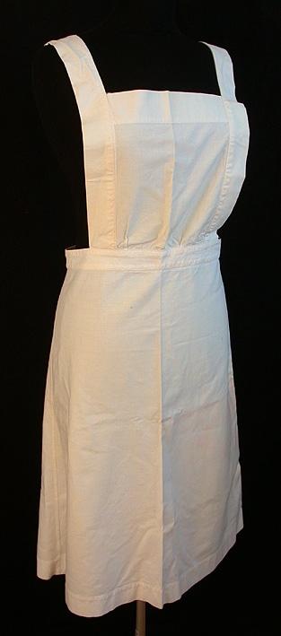 Vitt bomullsförkläde i 3 st våder. Bröstlapp med 2 st 590 mm långa band att placera över axlar, ned på rygg och knäppes fast i linningen baktill. Förlängd linning med vita plastknappar och handtränsade hål att knäppa i midjan.