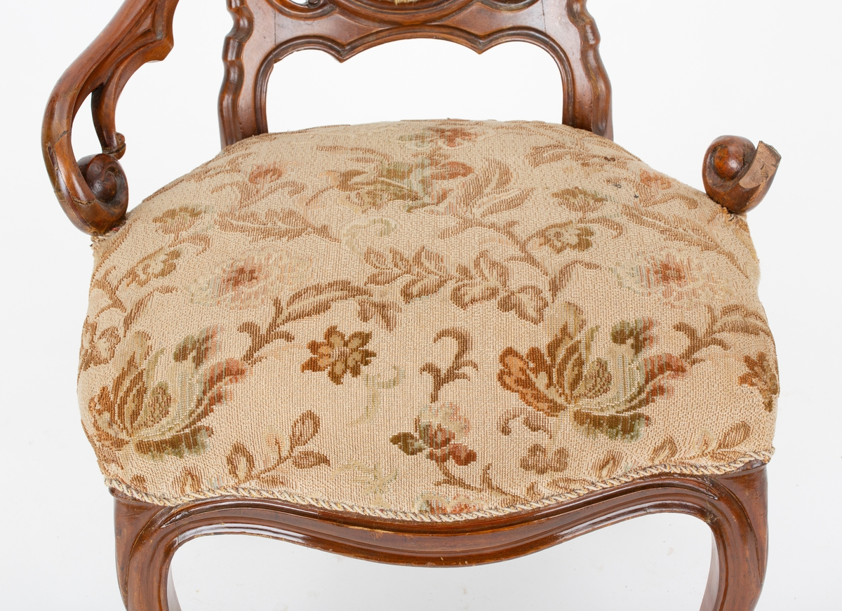 Stol med armlener. Stopp i sete og i rygg med speil. Utskjæringer, hjul på forben. Del av større møblement.