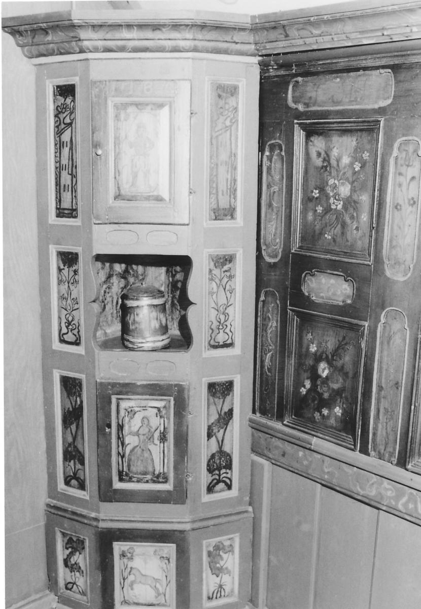 På sidene øverst hus, ellers trær; øverste dør: mann i vide bukser; dør nedenfor: kvinne, nederst: hest