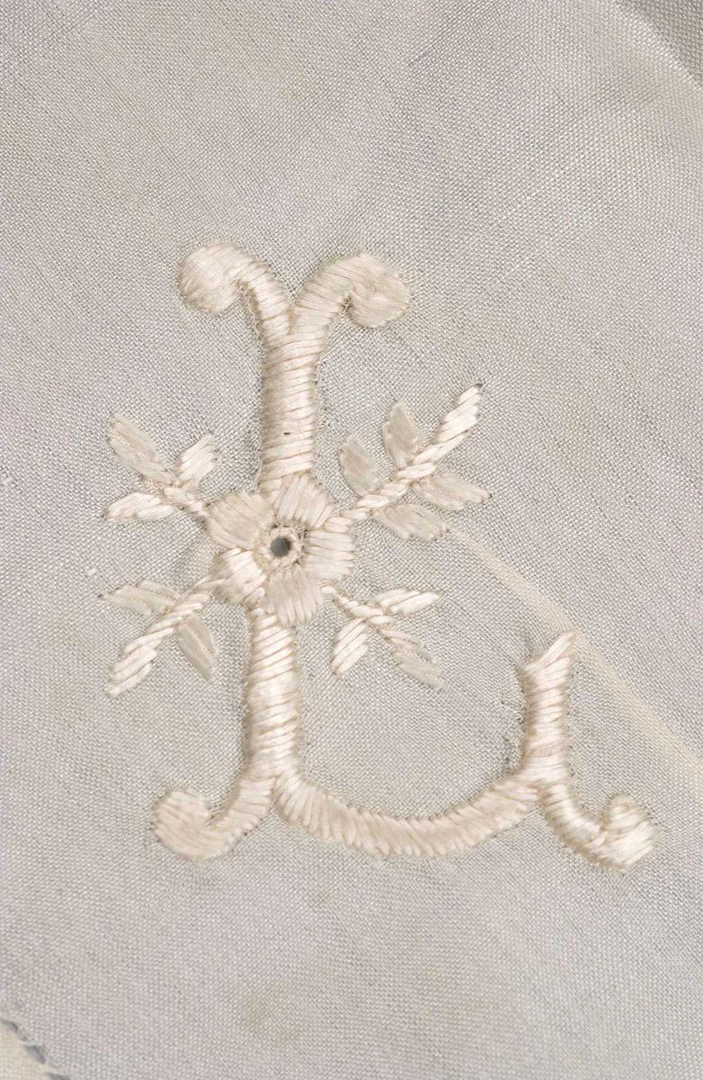 Hvitt silketørkle/pyntelommetørkle, kvadratisk form med brede kanter sydd opp med hullsøm. Brodert momogram L med blomst.
