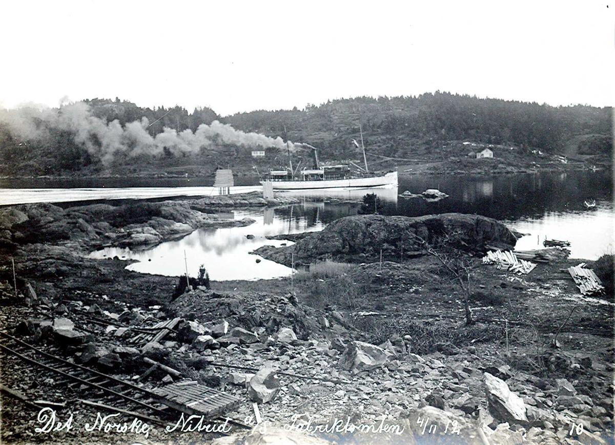 """""""04/11-1912"""" Nitriden. Planering og utfylling av fabrikktomten. Løsmasser fylles i buktene mellom skjærene. Fyrlykt nr. 612 i Norsk Fyrliste, bygd i 1894, flyttet til Friisøy, lenger vest, i 1929. En av kystens """"hvite svaner"""" (rutebåter) gjennom Tromøysund for vestgående. Skinneganger. Tromøy i bakgrunnen."""