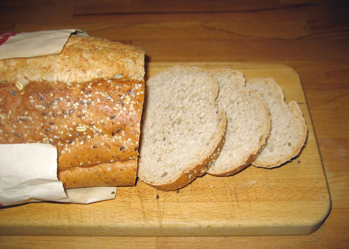 Forsiden: Et protrettfotografi av en baker i bakerklær. På fotografiet er en underskrift: Arild