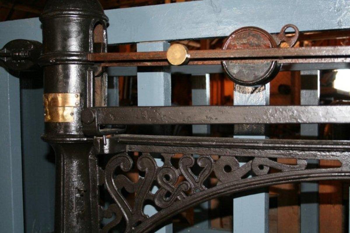 """Fundament med tett tregulv. To solide grinder utgjør langveggene. Kortveggene er tette. De er festet til grindene med jernbeslag. Kortveggene kan legges ned og fungerer som ramper for """"av- og påstigning"""". Veieinnretningen er montert på en støpt jernsåle. Dyrets vekt avleses på den vannrette armen."""