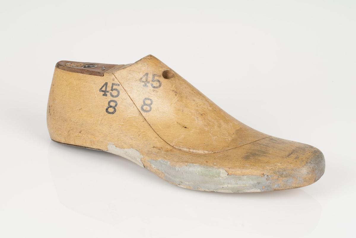 En tremodell i to deler; lest og opplest/overlest (kile). Høyrefot i skostørrelse 45, og 8 cm i vidde. Hælstykket i metall. Lestekam i skinn.