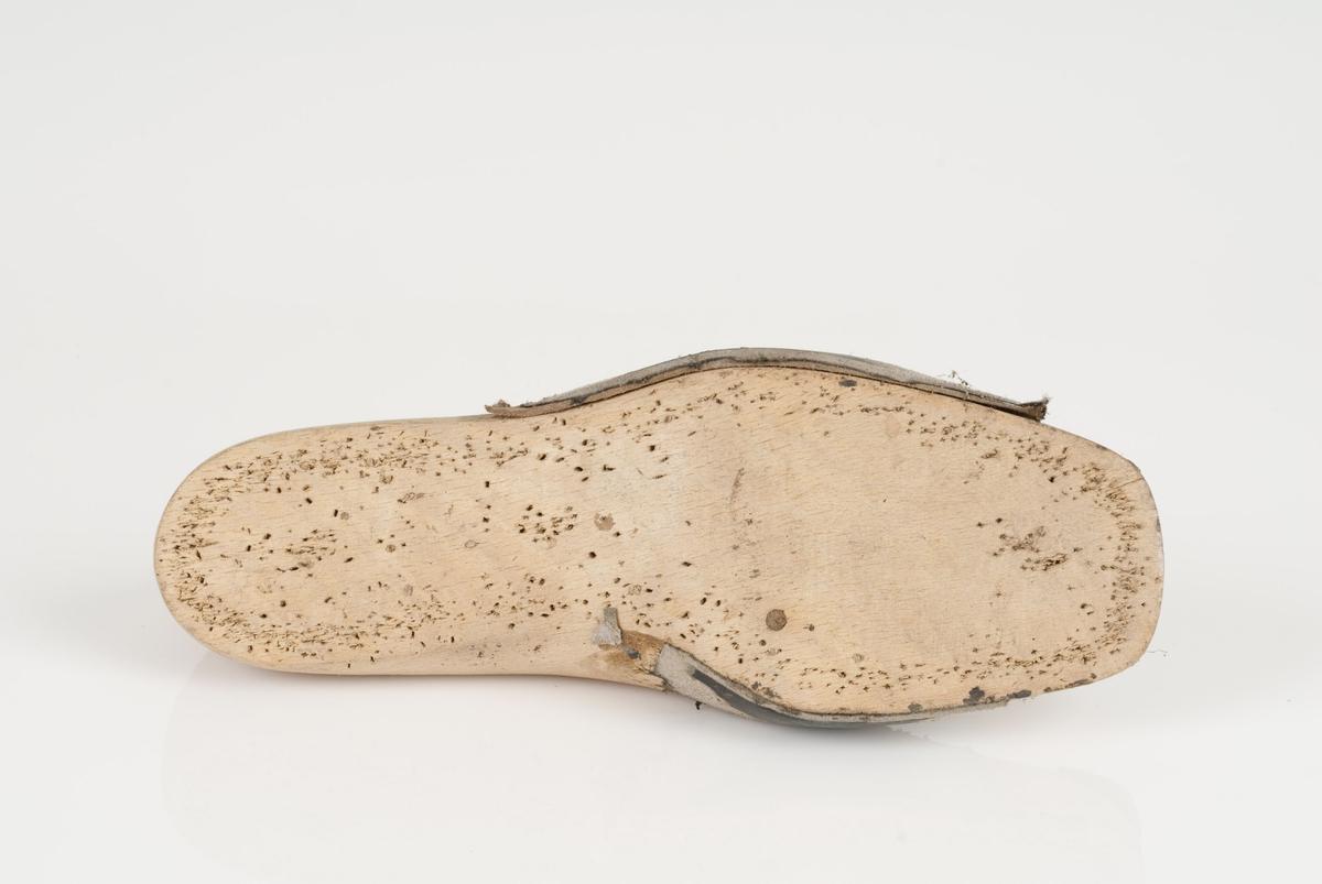 En tremodell i to deler; lest og opplest/overlest (kile), med påført tekst. Høyrefot i skostørrelse 36 med 7 cm i vidde. Det sitter noen skinnlapper på lesten.