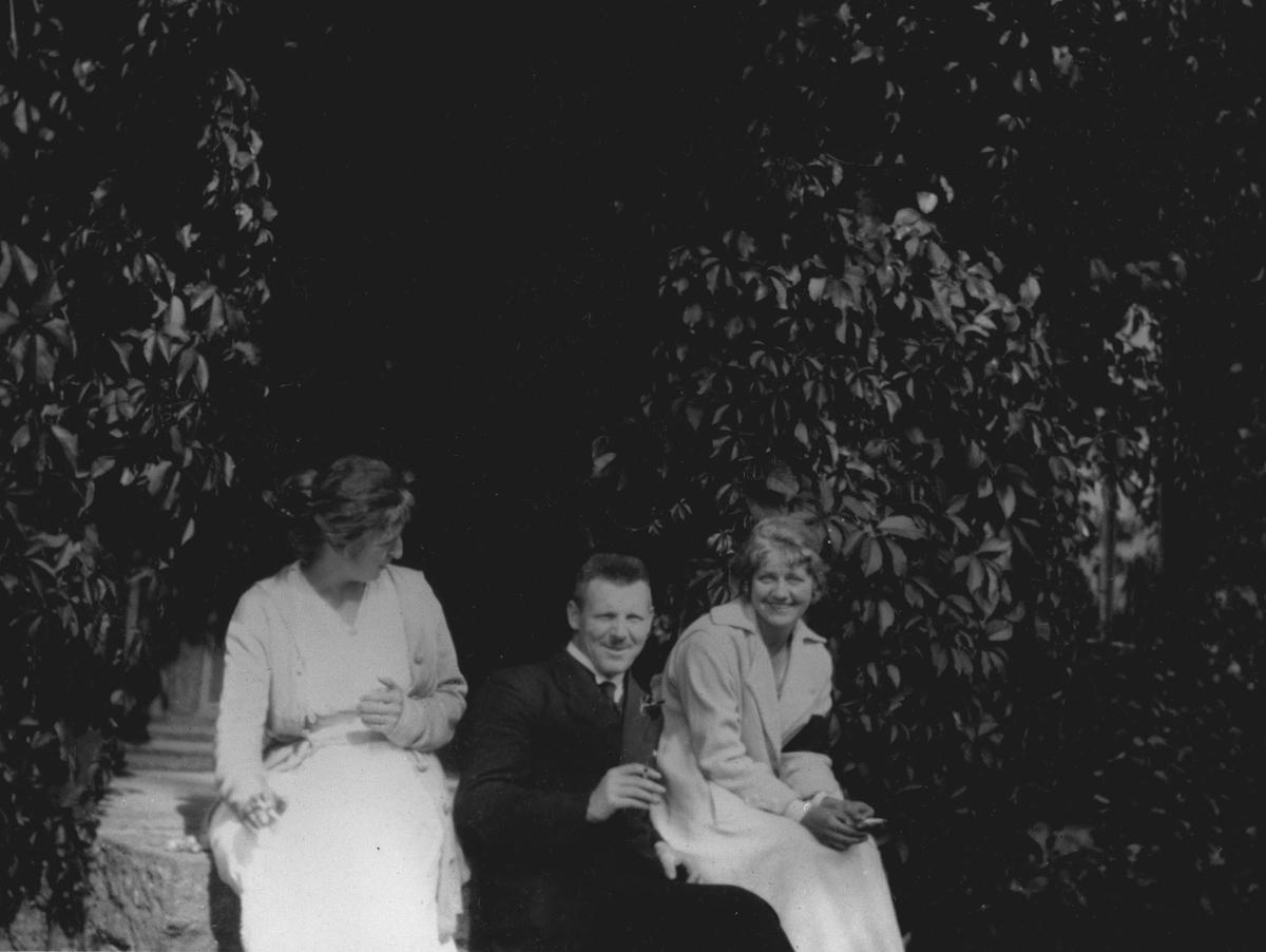 To kvinner og én mann i en frodig hage