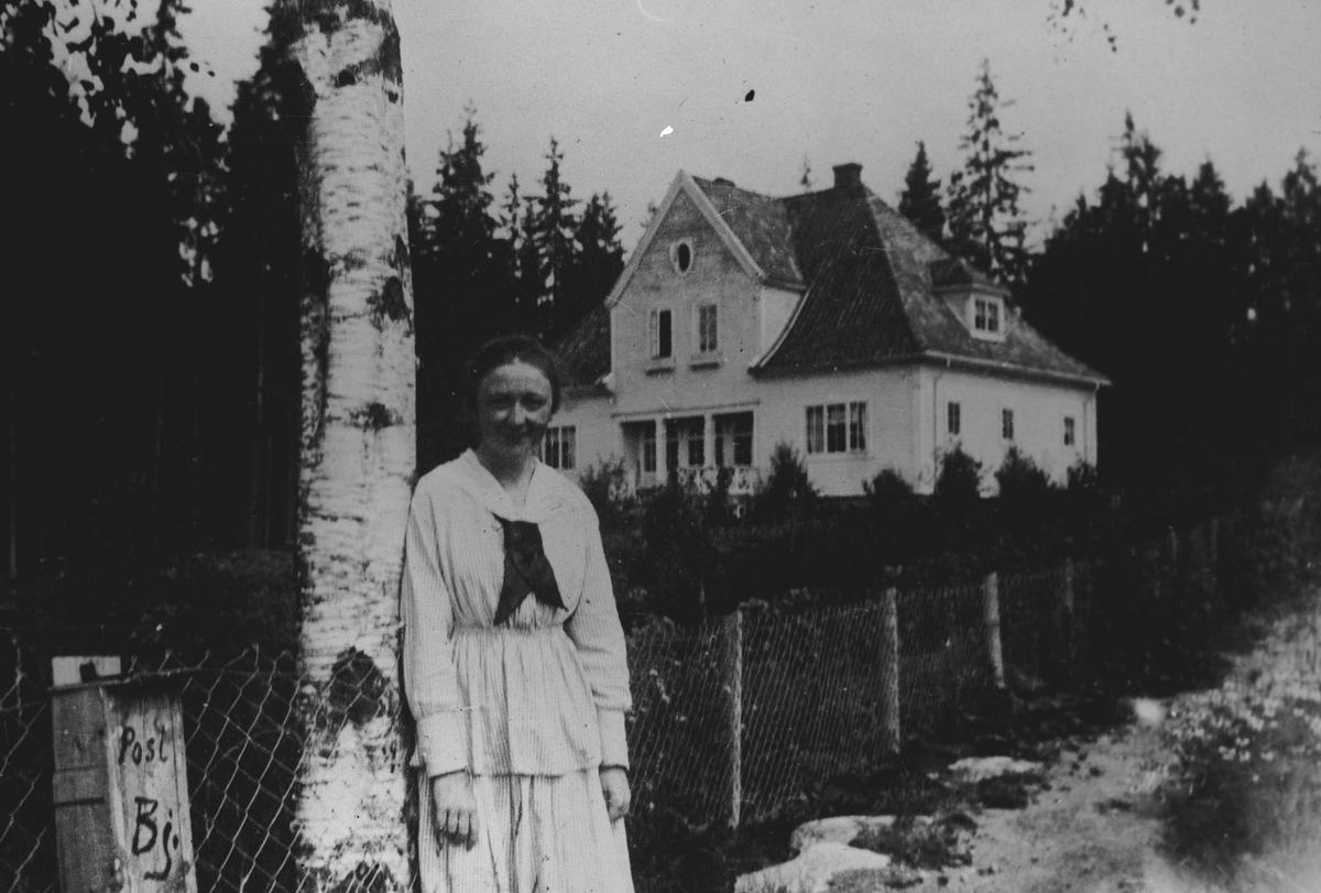 """""""Skjesets hus"""" med en kvinne foran (i dag)"""