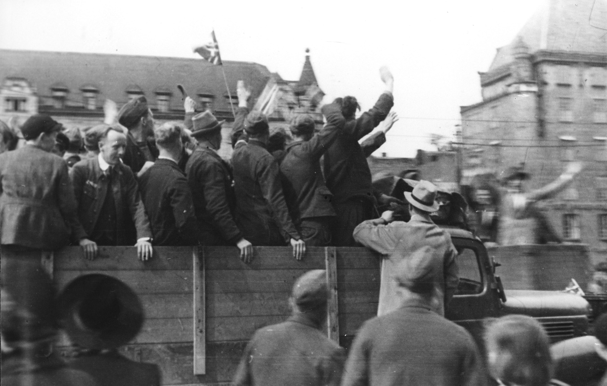 Soldater og sivile på et lasteplan omkranset av tilskuere som hilser og vifter med flagg. Antagelig frigjøringsfeiring i Oslo.