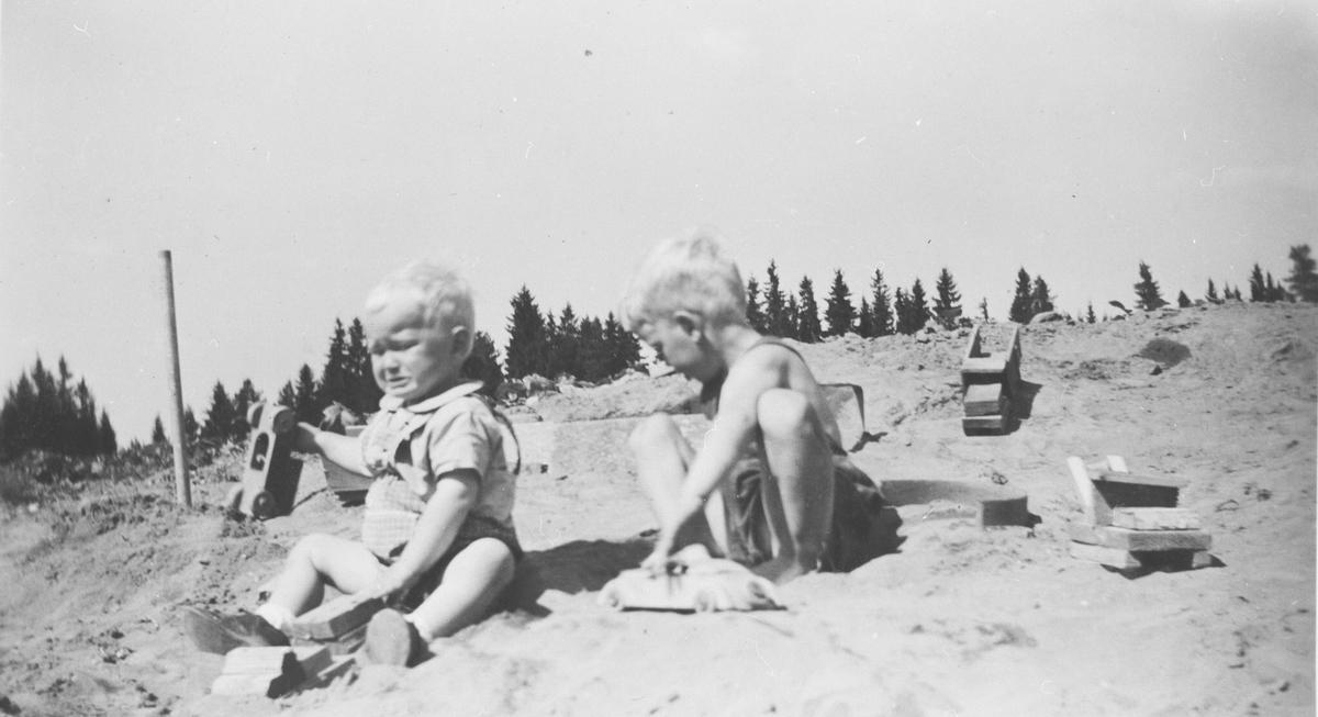 Barn leker med biler i sandhaug på Berger gård.