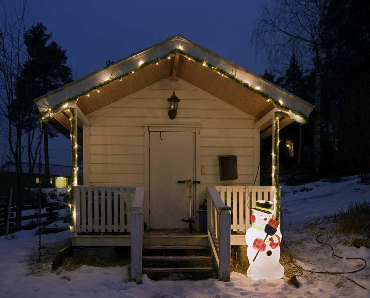 Julebelysning  Hvit julebelysning i girlander og lysende snømann ved dukkestue
