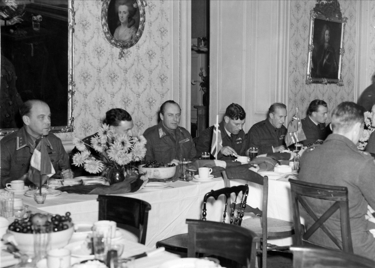 """HKH Kronprins Olav spiser lunsj med norske og utenlandske flyvere. Til venstre for kronprinsen sitter kaptein """"Zulu"""" Morris, sjef for 132 Wing."""