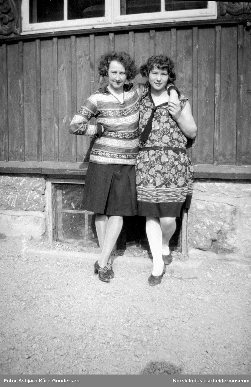 To kvinner i kameratslig positur foran en husvegg
