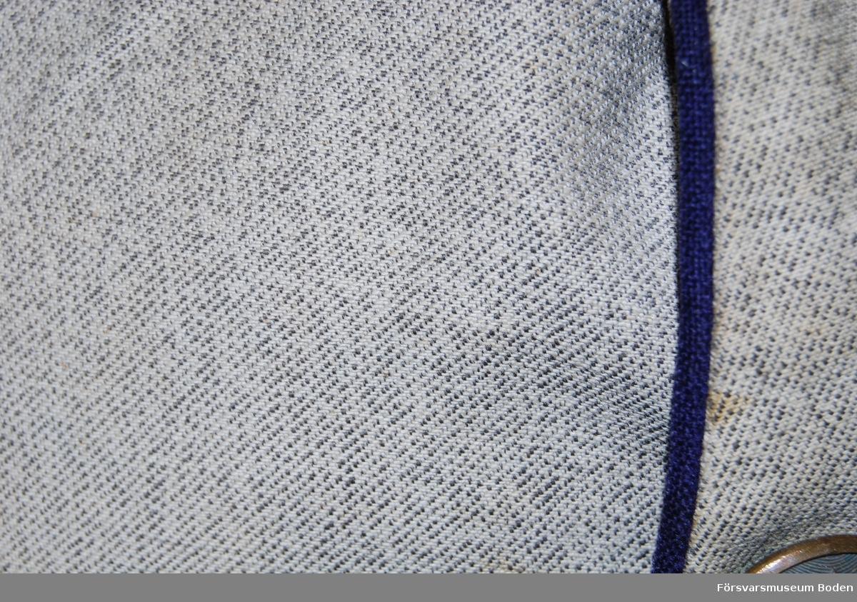 Ljusgrått linnetyg utan foder, typ lägerrock. Uppfällbar ståndkrage med blått kläde på överkragen och fyrkantsgalon i guld runt kanten. Ingen slejf eller tillhörande knappar vid kragen. Axeltränsar m/1910 med flätat beläggningssnöre i guld på svart matta. Valknut nertill och upptill mattförgylld knapp av kårens mindre modell, vilken är fastsydd på rocken. Tre metallstjärnor av silver betecknande kapten. Framtill blå passpoal och enkel rad med sex bronserade knappar av fortifikationens modell. Fyra insydda fickor med spetsformade lock utan knappar. Chevroner av blått kläde på ärmarnas nedre del, samt ett kort sprund med knapp av kårens mindre modell.