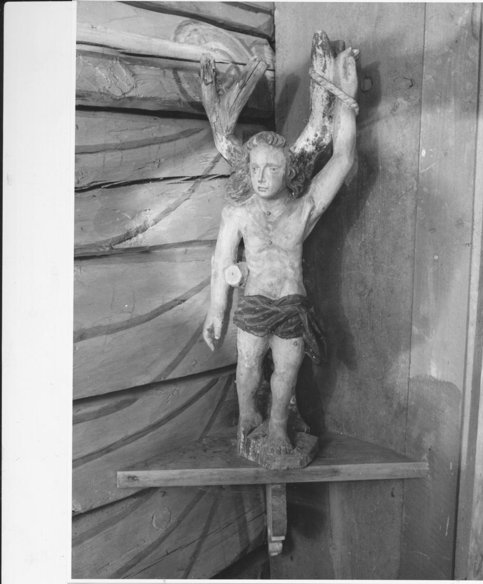 Den hellige Sebastian, naken, langt hår, lende- klede, høyre arm oppstrakt og bundet til et tre.