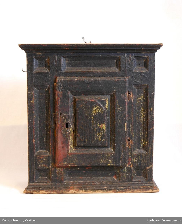 Skap til å henge på vegg. Profiler. Smidd låskasse med beslag. Låst, nøkkel mangler. Svartmalt, spor etter rød og gul maling under.